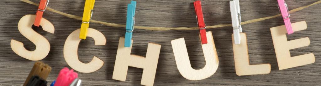 Schule aus Holzbuchstaben an der Wäscheleine